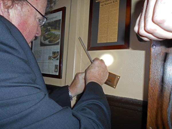 Det var den forhenværende cigar-sorterer og socialdemokratiske statsminister Thorvald Stauning, der blev hevet op af glemmeposen og synliggjort på væggen ved siden af Gitte Kiks bornholmerur. Det var lige nøjagtig her, at Stauning indtog sin medbragte madpakke under frokostpausen i Statsministeriet. På skiltet kan læses: 'STATSMINISTER THORVALD STAUNING var i mange år yndlingsoffer for SVIKMØLLEN, som fejrer sin 100 års fødselsdag i år. Opsat af Selskabet for Dansk Memorabilitet. December 2015'. Det er Kansleren, der trods indtagelse af adskillige dramme førte skruetrækkeren unden at ryste påp hånden. Foto©JørgenKoefoed.